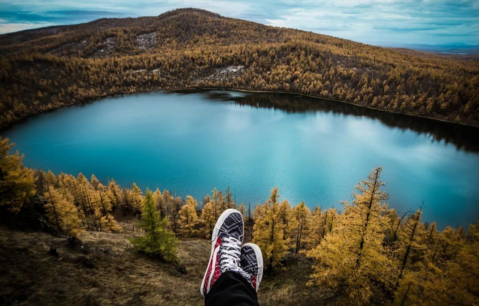 Travel pick of feet overlooking a lake. Well, the feet aren't actually doing the looking...
