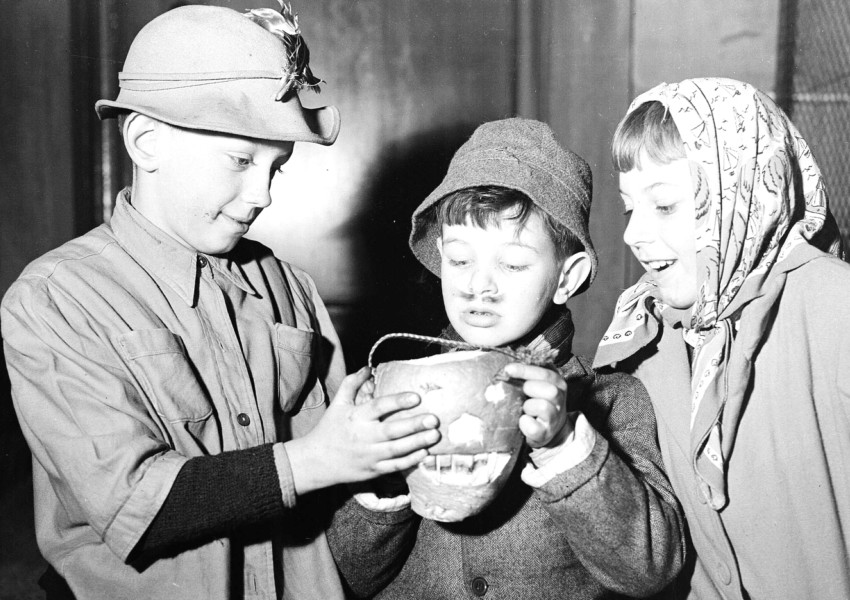 Three 1956-era children look at carved turnip.