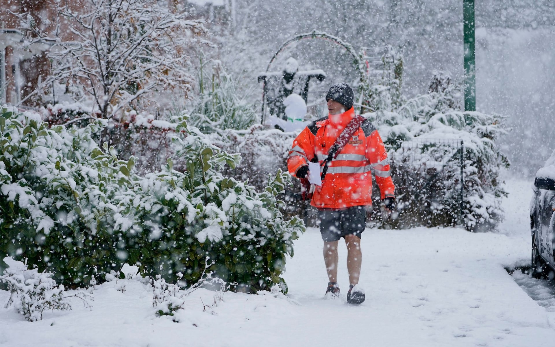 Mailman walking in snow.